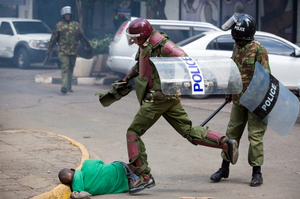 Kenyan police officers kick an unarmed protestor.